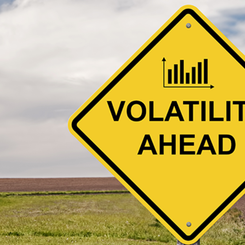 """Yellow diamond-shaped """"Volatility Ahead"""" sign in rural background"""