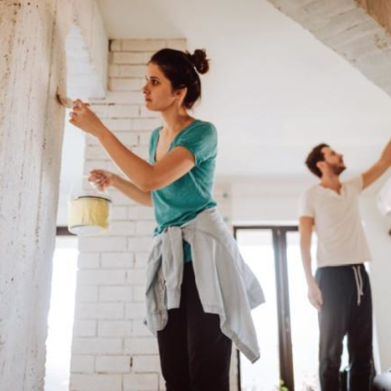 A young couple painting the interior of a home